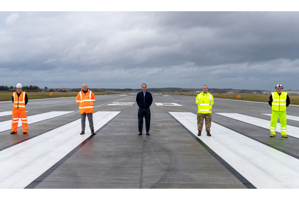 5 men standing in a line, distanced apart and wearing high visibility clothing.
