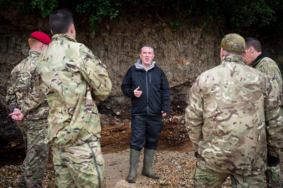 Richard Osgood talks to 4 soldiers in a rocky area of land.