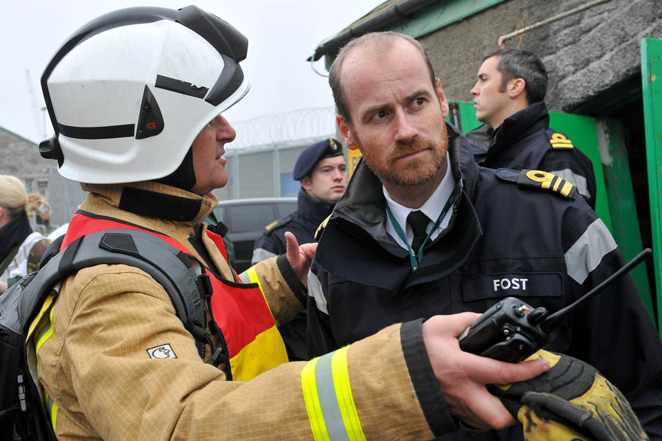 A member of the South Wales Fire and Rescue Service discusses options with a member of the Flag Officer Sea Training organisation