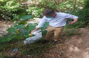 Ambassador picking plastic near a river