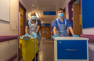 Image depicts two defence medics wheeling trollies down a hospital corridor.