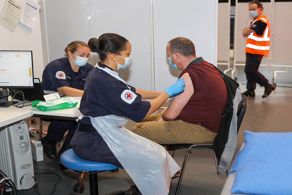 Image depicts a defence medic injecting a patron with a Covid-19 vaccine.