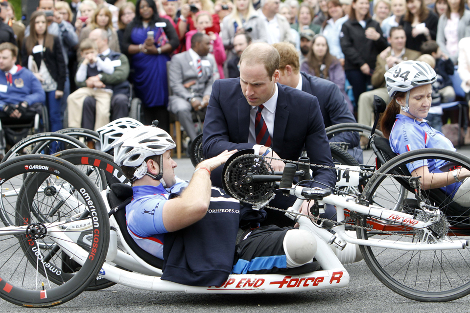 Prince William speaks with a wounded serviceman on a handcycle