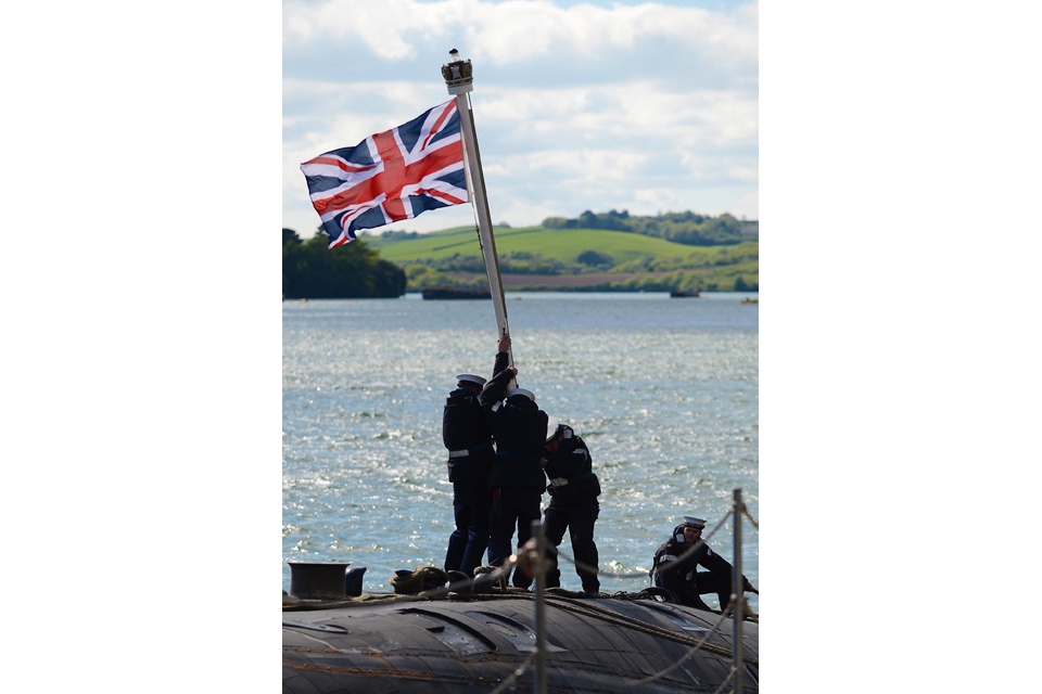 Submariners erect the Union Jack on HMS Trenchant's for'd casing