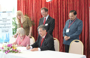 Susan Moore (CEO of STC Consortium Ltd) and Tunku Dato Seri Iskandar Abdullah (Group Executive Chairman of Melewar Group Berhad) sign the collaborative agreement at the British High Commissioner's Residence. Looking on are Pam Sutton (COO of STC Consortiu