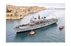 Tugs help to guide HMS Illustrious into the port of Valletta