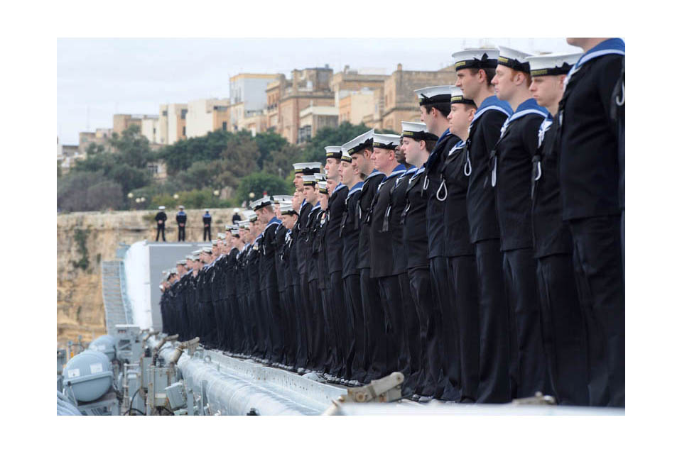 Sailors line the deck of HMS Illustrious