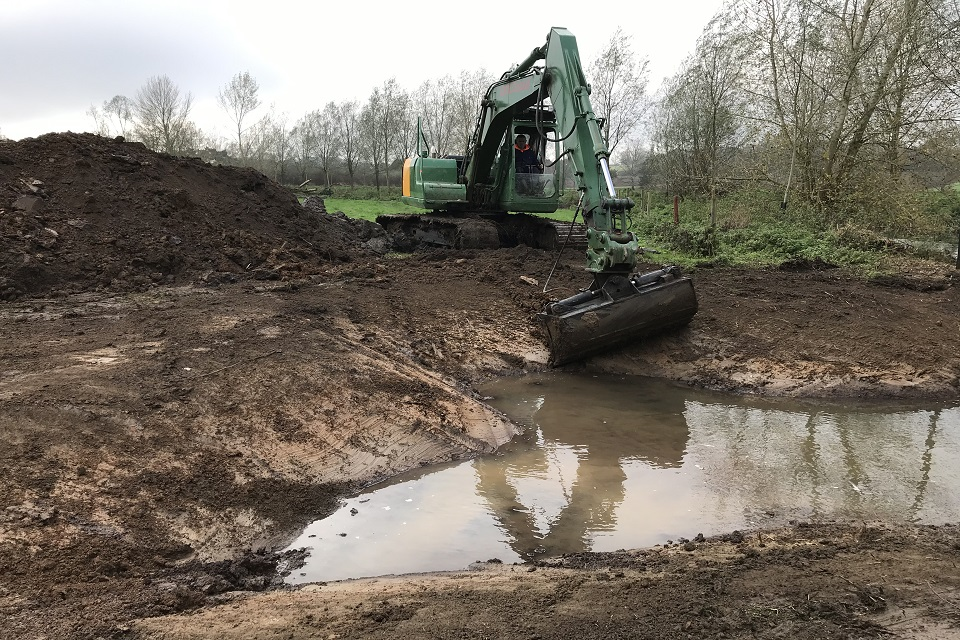 A digger being used to create a backwater.