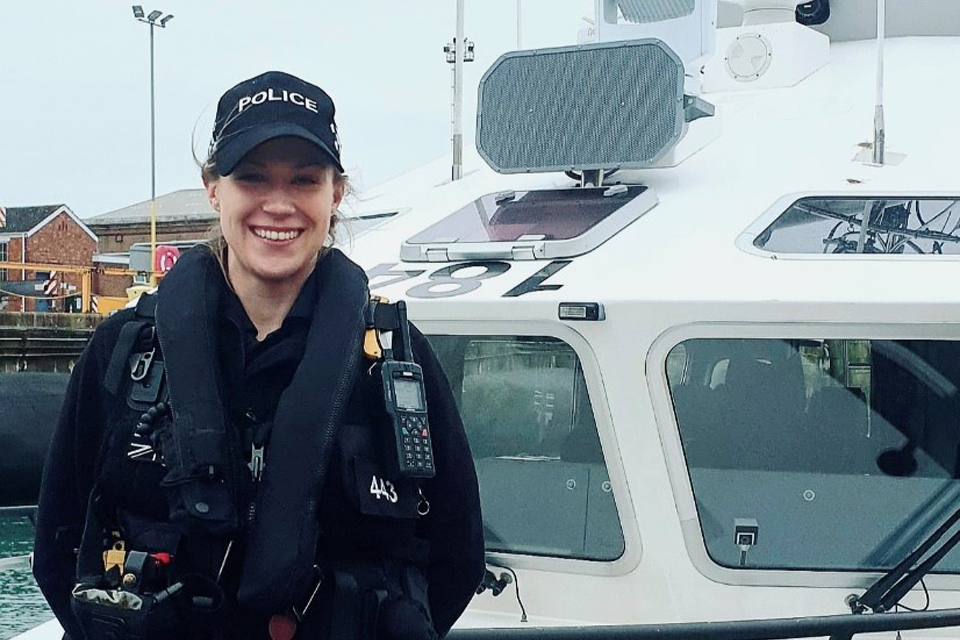 Kirsty in her MDP uniform stands outside a police boat.