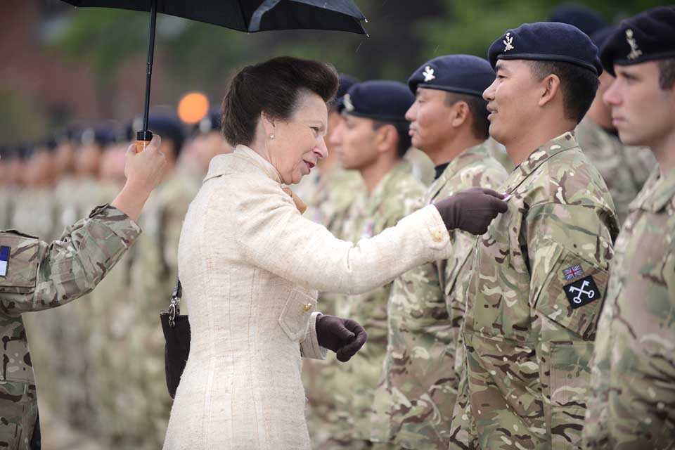 Princess Anne pins a medal to the chest of a soldier
