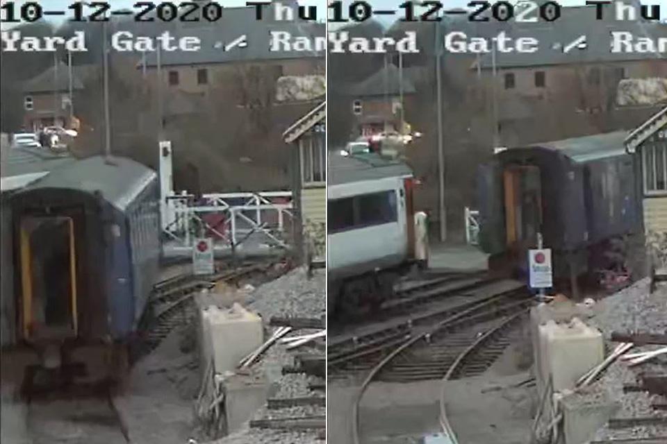 Railway vehicle moving along track towards gate.