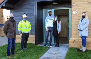 The photo shows a young man and woman being welcomed to their new home by a property developer and two members of the local Community Land Trust.