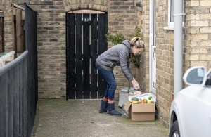 Volunteer leaving groceries outside someone's house.