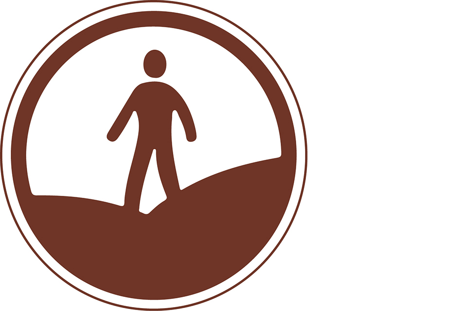 Round brown symbol with a person walking over hills