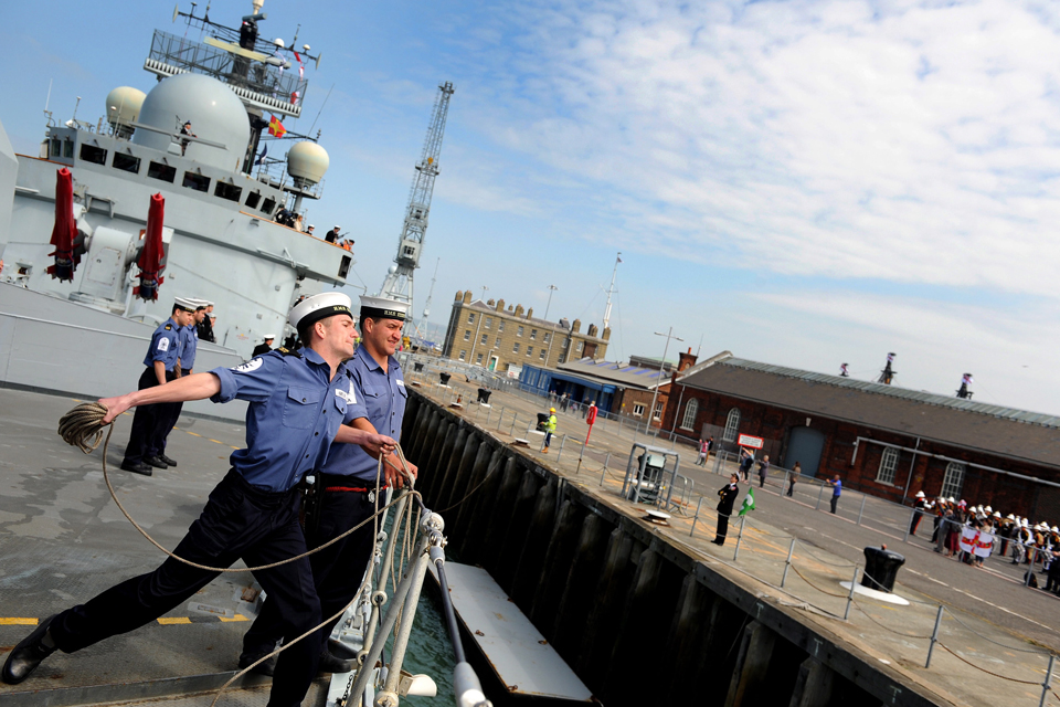 A sailor throws a heaving line from HMS Edinburgh