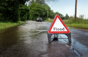 flood sign in front of a flooded road and car