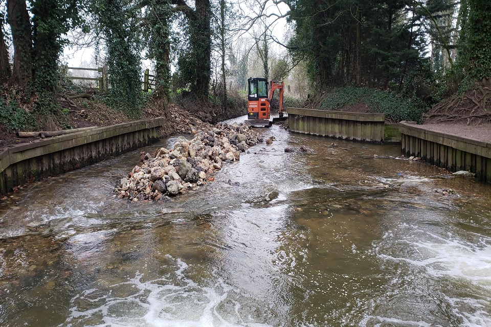 The chalk stream with a digger working on the fish pass.