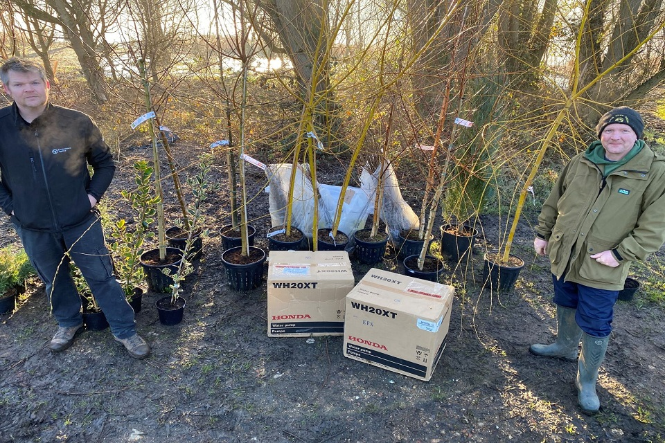 Our fisheries officer standing by some of the trees given to a fishery and a representative from the fishery.