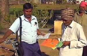 A postman delivers leaflets on eggplant borer control to a farmer