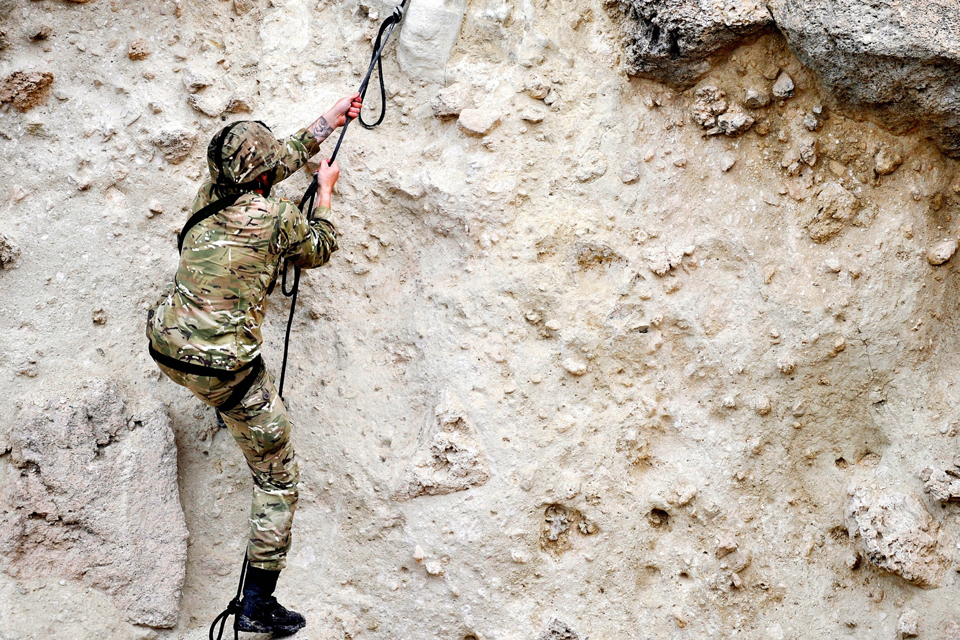 A Royal Marines commando scales a cliffside