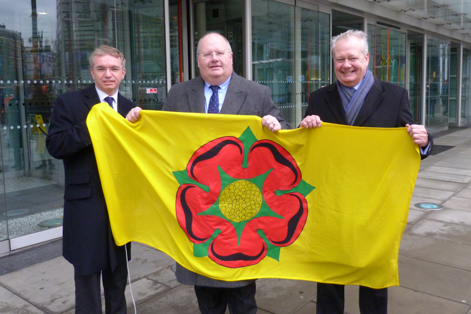 Eric Pickles holding the flag of Lancashire with two Lancashire MPs