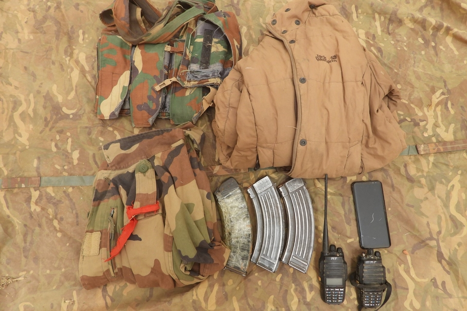 Clothing including camouflaged jackets as well as AK47 magazines and radios are laid out after being found in the search.