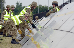 Personnel from 143 (West Midlands) Brigade erect a flood defence barrier at the National Grid gas compressor station at Alrewas during the exercise [Picture: Sergeant Russ Nolan RLC, Crown copyright]