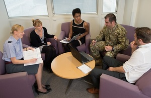 5 military and civilian personnel sit around a table in a meeting room.