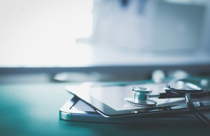 Picture of a mobile device and a stethoscope on a table.