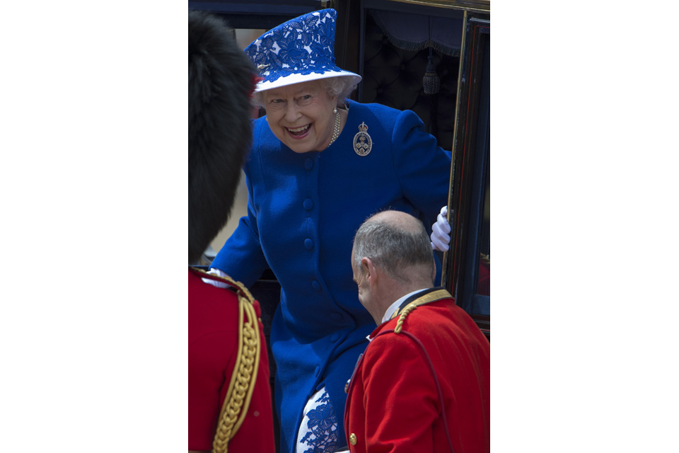 Her Majesty The Queen smiles as she steps from her carriage