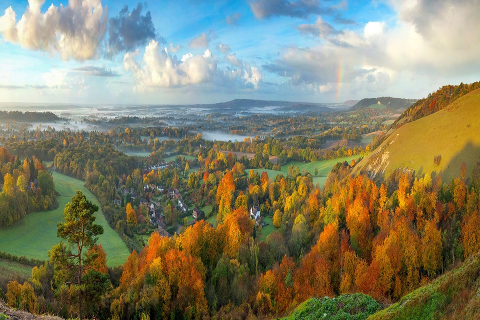 Image shows a tall hill lit by the morning sun to the left with above a landscape of autumnal trees. There is mist above the fields in the distance and a rainbow can be seen to the right