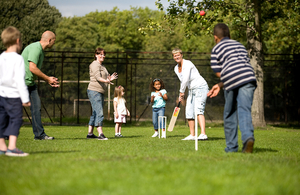 Group of people of different ages playing cricket in a garden