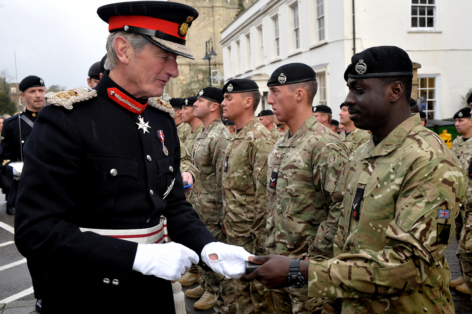 Lord Tollemache presents a soldier with a medal