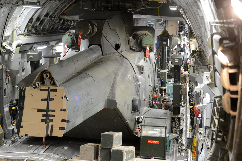 An RAF Merlin helicopter being packed and secured in a C-17 Globemaster aircraft