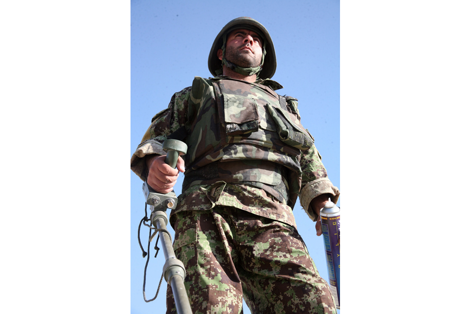 An Afghan soldier carries a metal detector