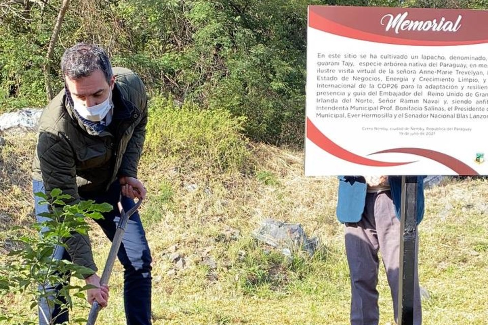 HMA Navai using a spade to plant a tree, standing by the memorial sign that commemorates the occasion