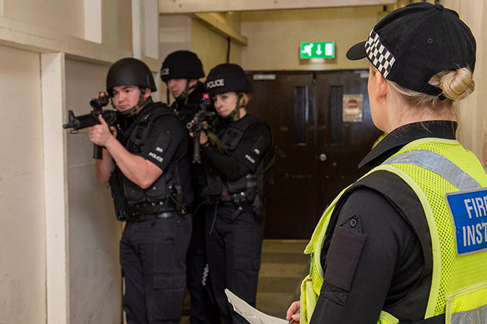 3 uniformed MDP police officers inside a building hallway holding firearms. A firearms training officer stands by.