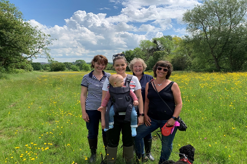На изображении изображены четыре женщины из семьи Джонсонов, а также ребенок и маленькая черная собачка в поле высокой травы и полевых цветов.