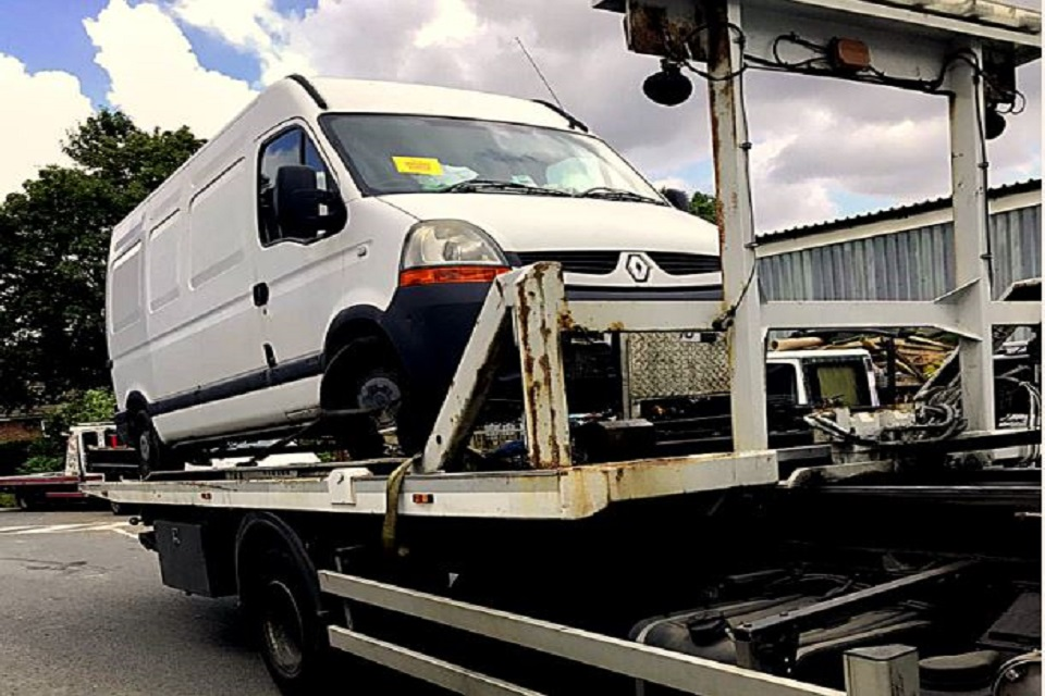 Image shows large white panel van loaded on the back of a transporter