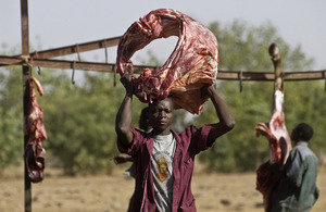 Man carrying meat at abattoir in Burkina Faso