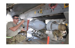 A Royal Air Force technician attaches a Paveway IV laser-guided bomb to the underside of a Tornado GR4