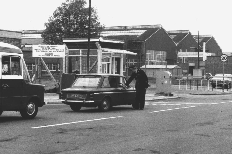 Black and white image of Ministry of Defence Police officer carrying out gate duties, alongside an arriving vehicle