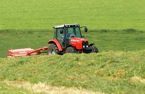 Red tractor in field of green.