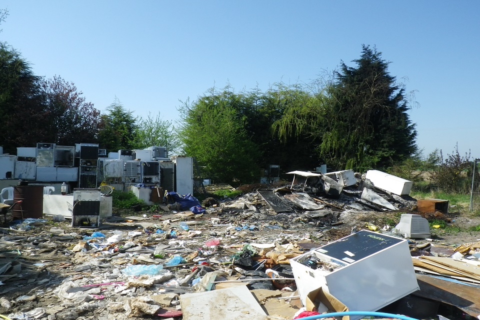 Image shows fridges stacked on the ground to the right of the picture with more fridges to the right that have been burned on a bonfire. General rubbish litters the foreground