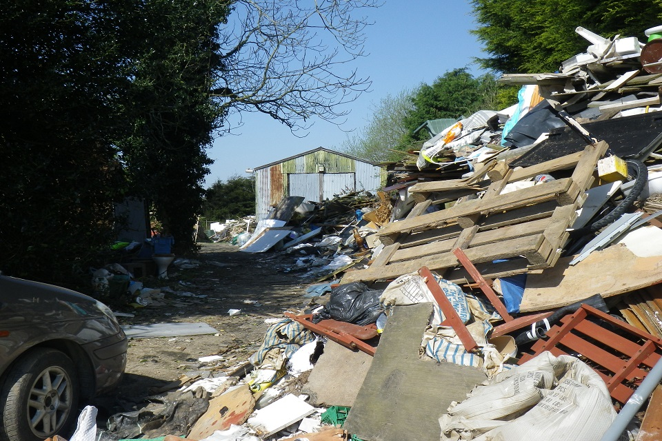 Image shows a stack of waste several metres high comprising furniture, wood and plastic. The front of a car can be seen to the left and a warehouse to the rear.