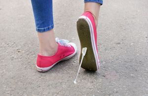 Chewing gum stuck to the bottom of a shoe of a person walking in the street