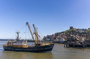 Fishing vessel in the sea overlooking coastal town