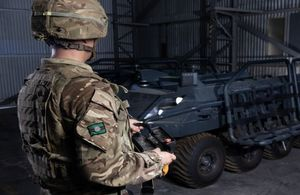 Army soldier holds remote to control computer-driven equipment