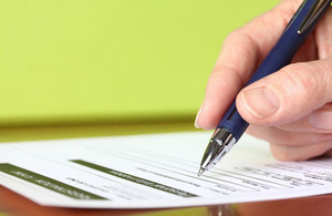 Hand with pen signing an application form