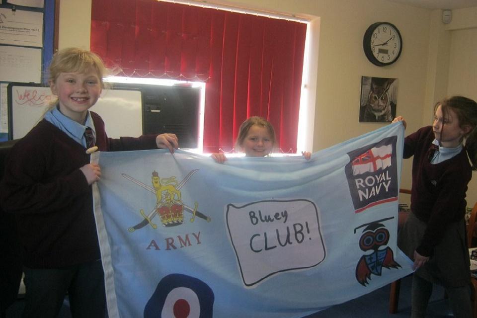 3 ребенка-члена Bluey Club держат флаг